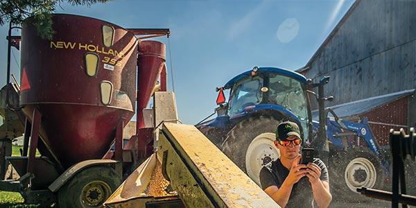 Homme devant un tracteur qui lit son smartphone