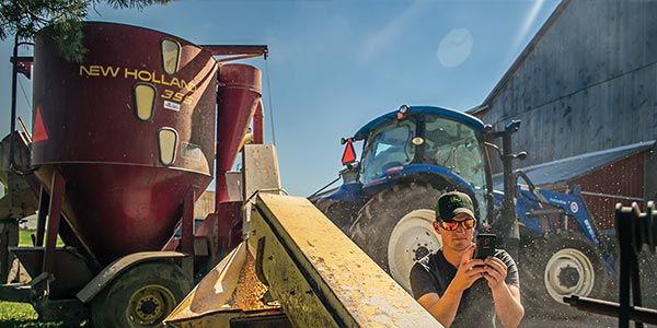 Man with smartphone in front of tractor