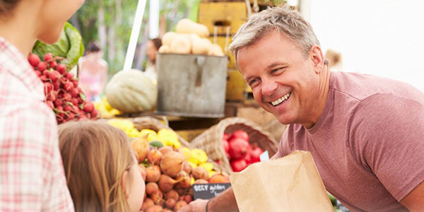 Man at farmer's market interacts with customers