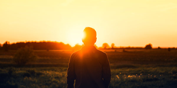 man in field at sunrise