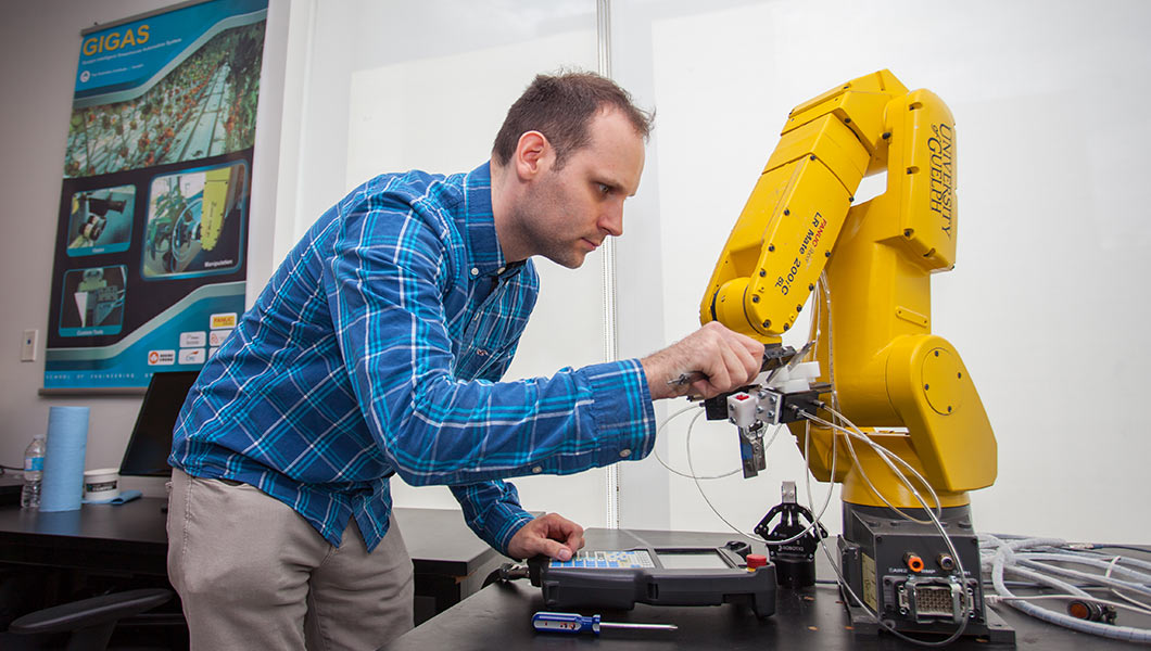 Patrick Wspanialy makes adjustments to robotic arm