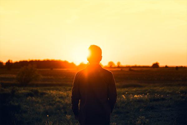 homme dans un champ durant une levé de soleil